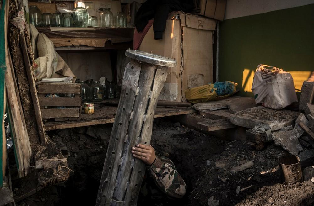 Ополченец в Иловайске демонстрирует нью-йоркским чеченоказакам кассетный боеприпас.